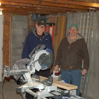 The owners of Battle Hill standing behind a radial arm saw